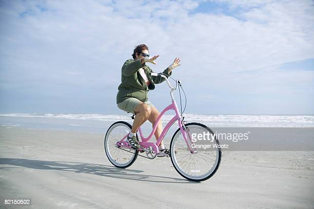 senior woman riding bicycle on beach - hands free cycling stock pictures, royalty-free photos & images