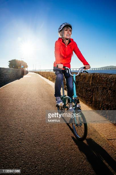 senior woman riding bike on cycle path - foldable stock pictures, royalty-free photos & images