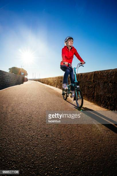 Senior woman riding bike on cycle path