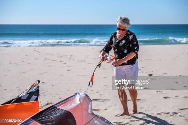 senior woman rigging her kite for kitesurfing - finn bjurvoll photos et images de collection