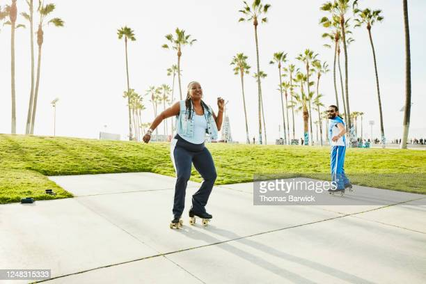senior woman roller skating with friends in park - disruptaging foto e immagini stock
