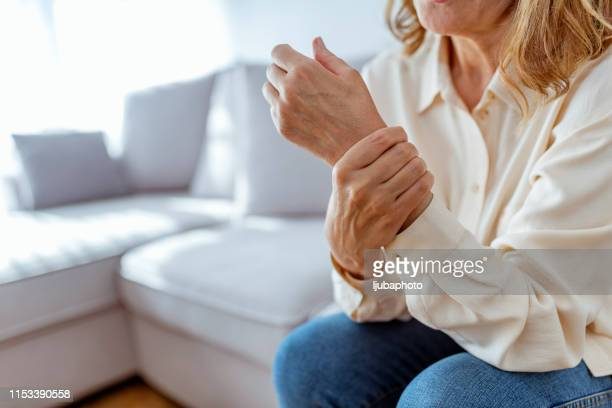 senior woman rubbing her wrist and arm suffering from rheumatism - wrist stock pictures, royalty-free photos & images