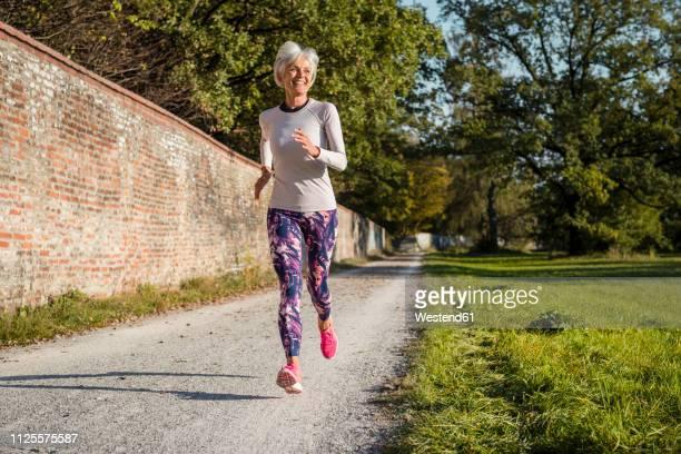 senior woman running along brick wall in a park - só uma mulher idosa imagens e fotografias de stock