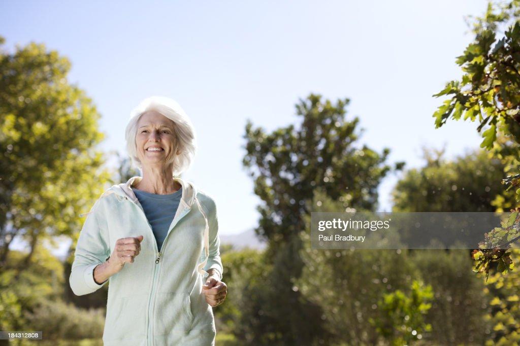 Senior woman running in park : Stock Photo