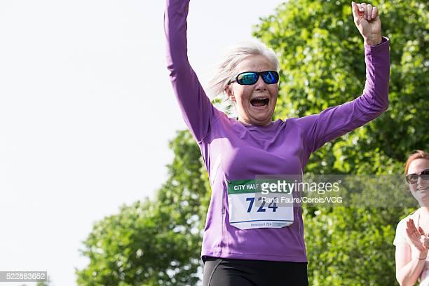 senior woman running in road race yelling with satisfaction - ハーフマラソン ストックフォトと画像