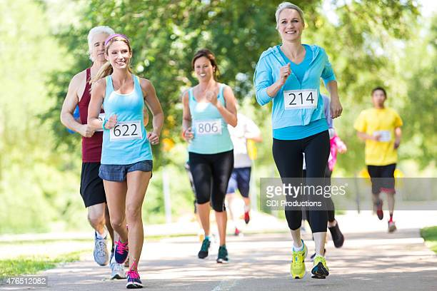 Senior woman running with diverse race contestants outdoors