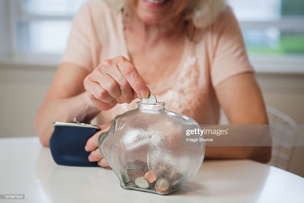 Senior woman saving money in piggy bank : Stock Photo