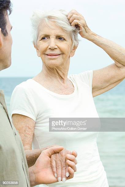 Senior woman scratching head and holding adult son's hand, sea in background