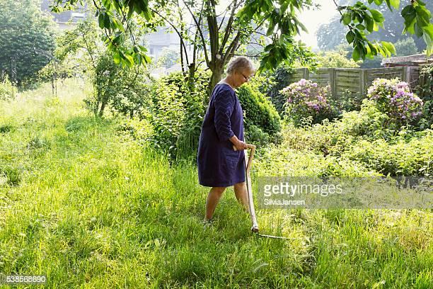 Ältere Frau mähen Wiese im Garten