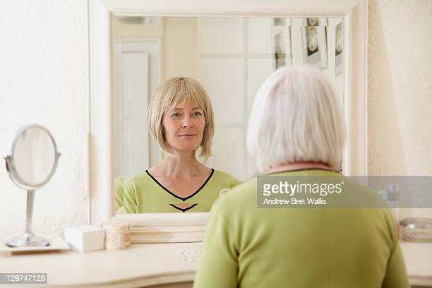 senior woman sees her younger face in the mirror