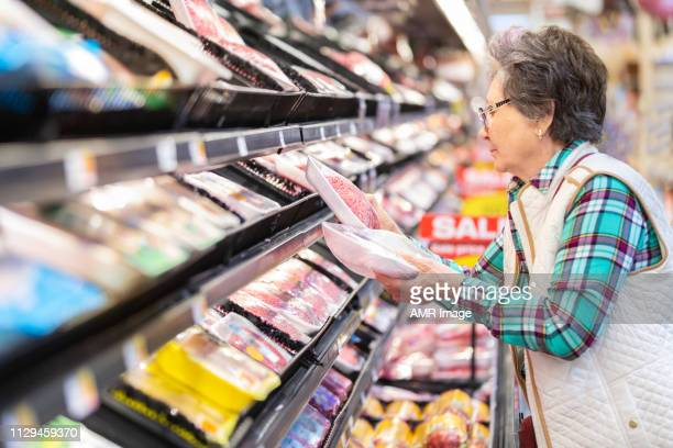 senior woman selecting ground beef in the meat department. - meat stock pictures, royalty-free photos & images
