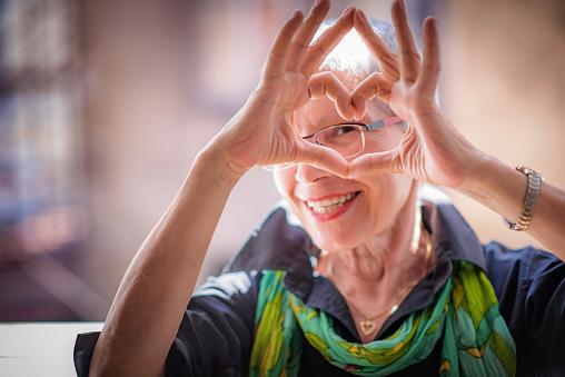 Senior woman sending love 894074170