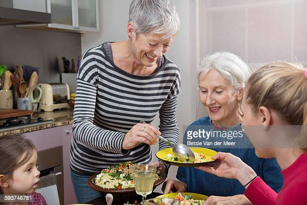 senior woman serves food to family at table. - british granny stock photos and pictures
