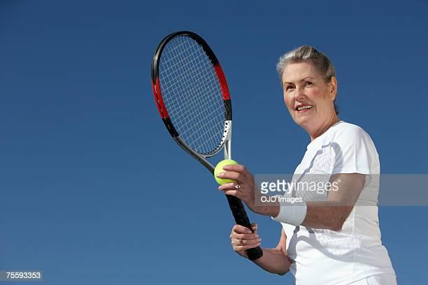 senior femme servant une balle de tennis - raquette de tennis photos et images de collection
