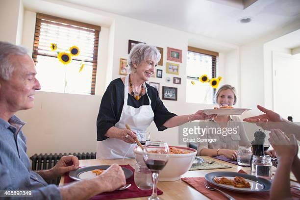 Senior woman serving food at family dinner