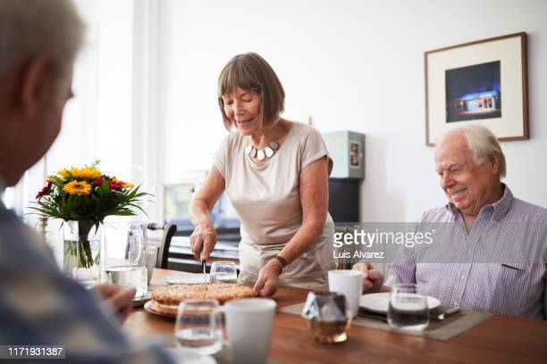 senior woman serving food to friends at home - guest stock pictures, royalty-free photos & images