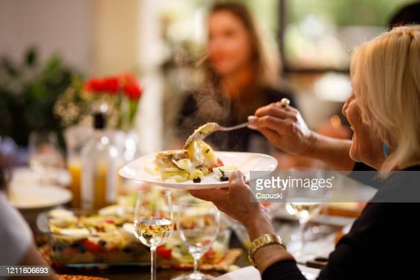 senior woman serving fresh hot food on easter - easter dinner stock pictures, royalty-free photos & images