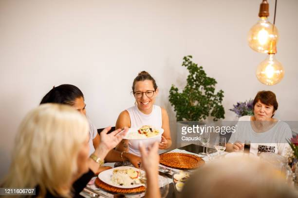 senior woman serving people on table - easter dinner stock pictures, royalty-free photos & images