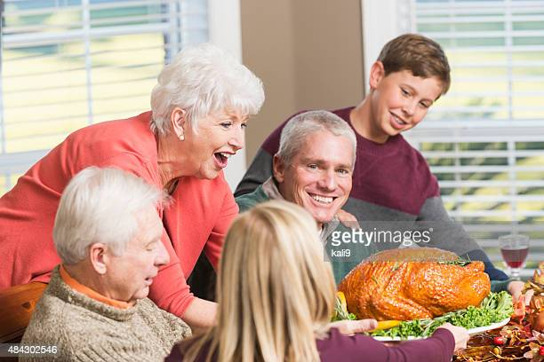 Senior woman serving roasted turkey to big family