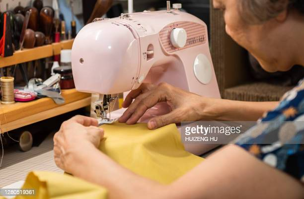 senior woman sewing on a sewing machine - sewing stock pictures, royalty-free photos & images