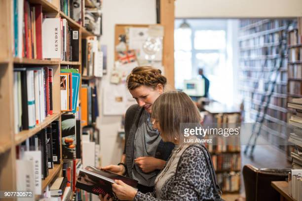 Senior woman sharing book with young female