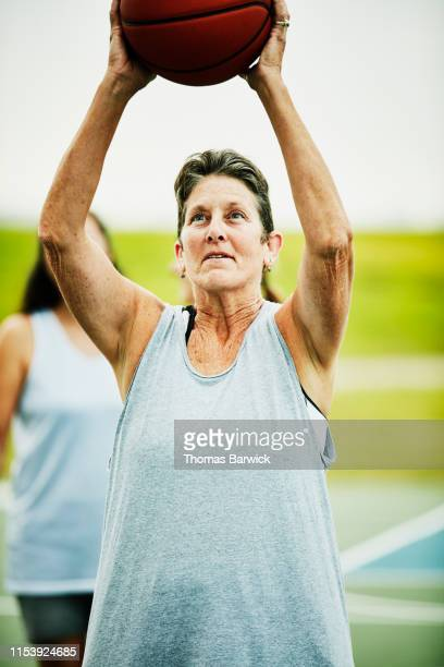 senior woman shooting free throw during early morning basketball game with friends - hitting stock pictures, royalty-free photos & images