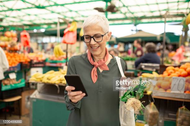 senior woman shopping at the farmer's market - market retail space stock pictures, royalty-free photos & images