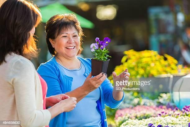年配の女性のショッピング、鉢植えの植物と花