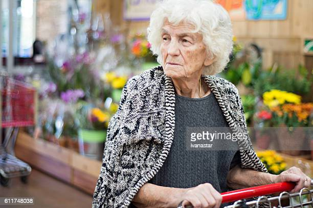 senior woman shopping in grocery store - one senior woman only stock pictures, royalty-free photos & images