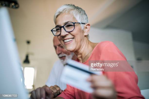 senior woman shopping online - bank account stock pictures, royalty-free photos & images