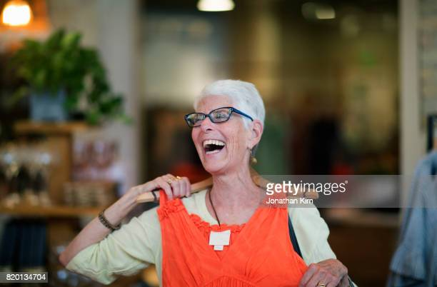 senior woman shops. - orange dress stock pictures, royalty-free photos & images