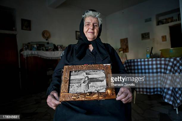 CONTENT] Senior woman showing a photograph of her when she was 20 years old carrying a wooden table on her back Mani Greece