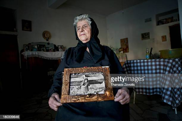 CONTENT] Senior woman showing a photograph of her when she was 20 years old carrying a wooden table on her back ManiGreece 2013