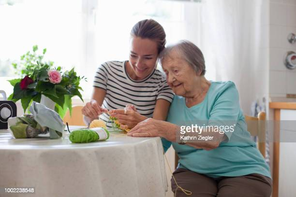 senior woman showing her adult granddaughter how to crochet - crochet stock pictures, royalty-free photos & images