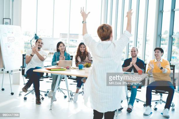 senior woman showing respect while team applauding congratulating appreciation and employee recognition concept,business successful concept - admiration stock pictures, royalty-free photos & images