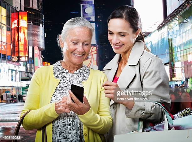 Senior woman showing woman message on mobile phone