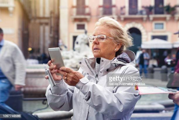 Senior woman sightseeing and using her cell phone with an extra battery connected in Italy