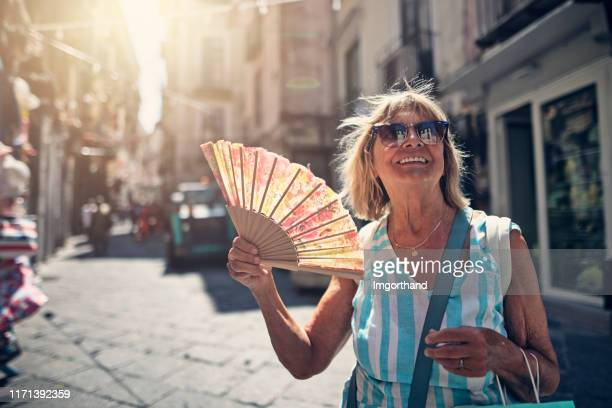 senior woman sightseeing small italian town - hand fan stock pictures, royalty-free photos & images