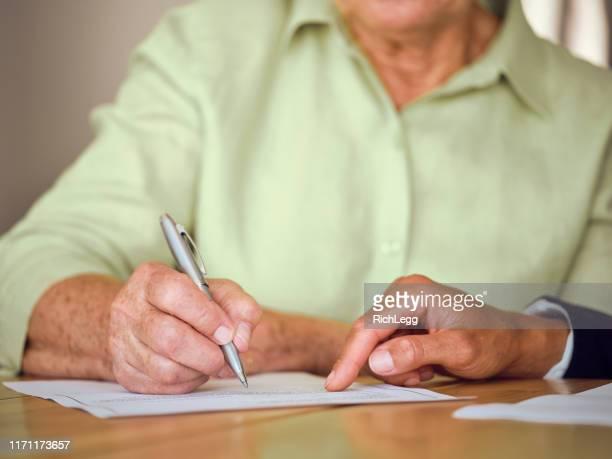originais de assinatura da mulher sênior em sua home - documento legal - fotografias e filmes do acervo