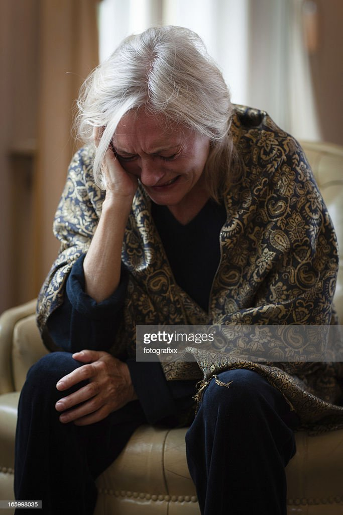 senior woman sits alone in living room and cry : Stock Photo