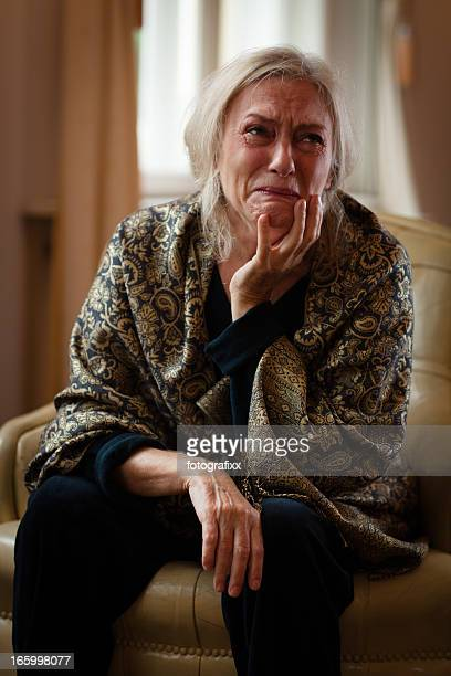 senior woman sits alone in living room and cry