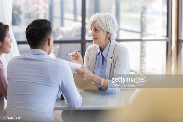 a senior woman sits at a table and talks with young woman - wealth stock pictures, royalty-free photos & images