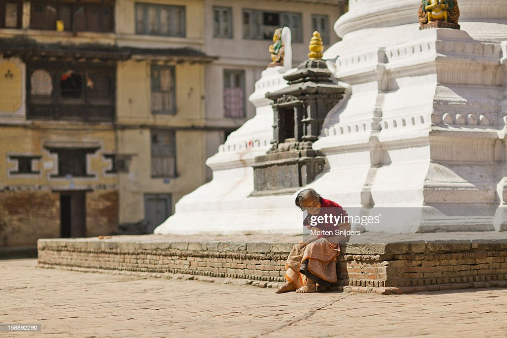 Senior woman sits at foot of stupa : Stockfoto