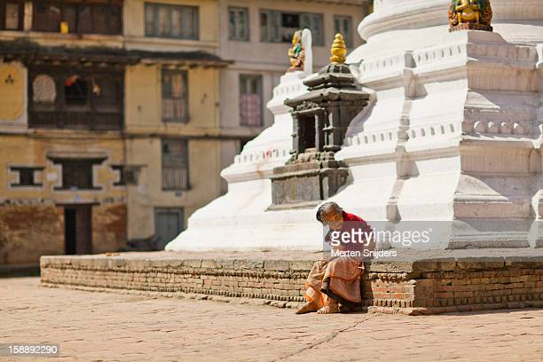 senior woman sits at foot of stupa - merten snijders stock pictures, royalty-free photos & images