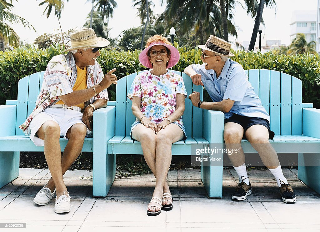 Senior Woman Sits on a Patio Chair Between Two Senior Men Talking to Each Other : Stock Photo