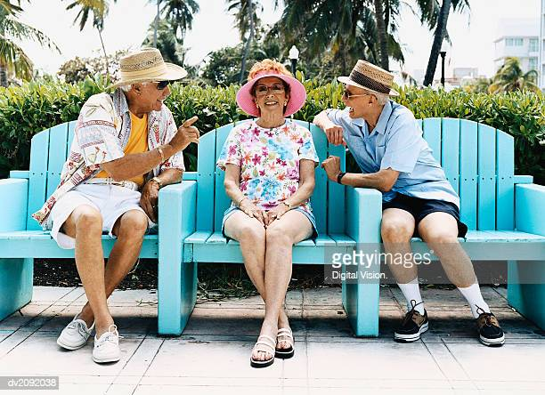 Senior Woman Sits on a Patio Chair Between Two Senior Men Talking to Each Other