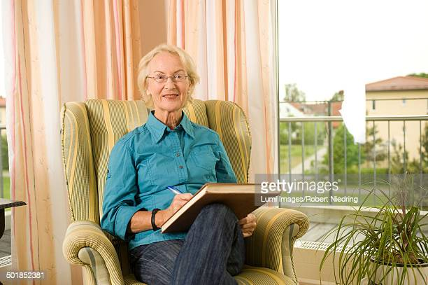 Senior woman sits with book in armchair, Bavaria, Germany