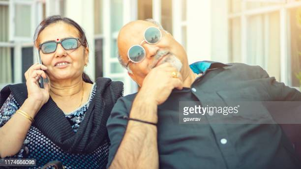 senior woman sits with her husband and talks on smartphone. - indian couples stock pictures, royalty-free photos & images