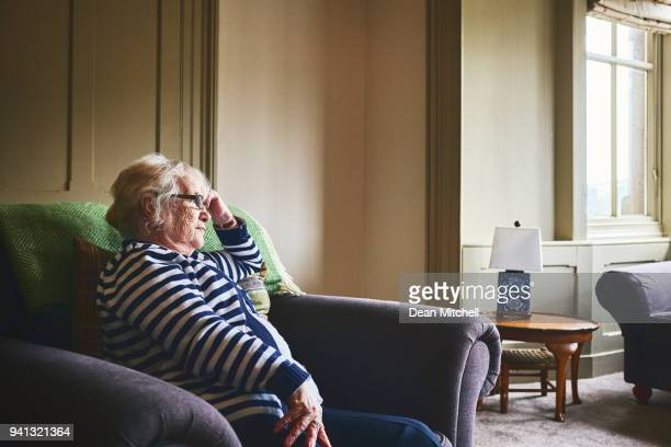 senior woman sitting alone at home - loneliness stock pictures, royalty-free photos & images