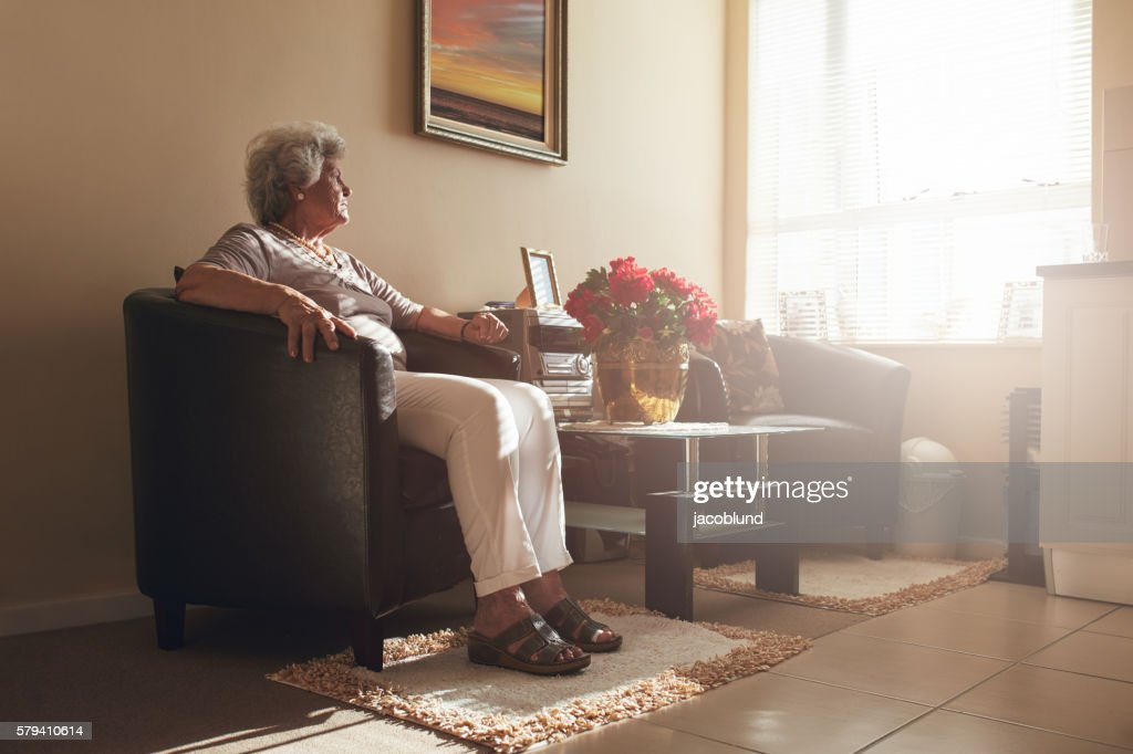 Senior woman sitting alone on a chair at home : Stock Photo